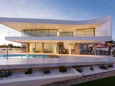 Illuminated luxury villa and pool at early evening