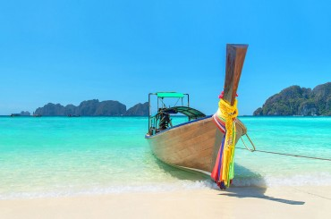 Long tail boat anchored on a golden beach in Phuket