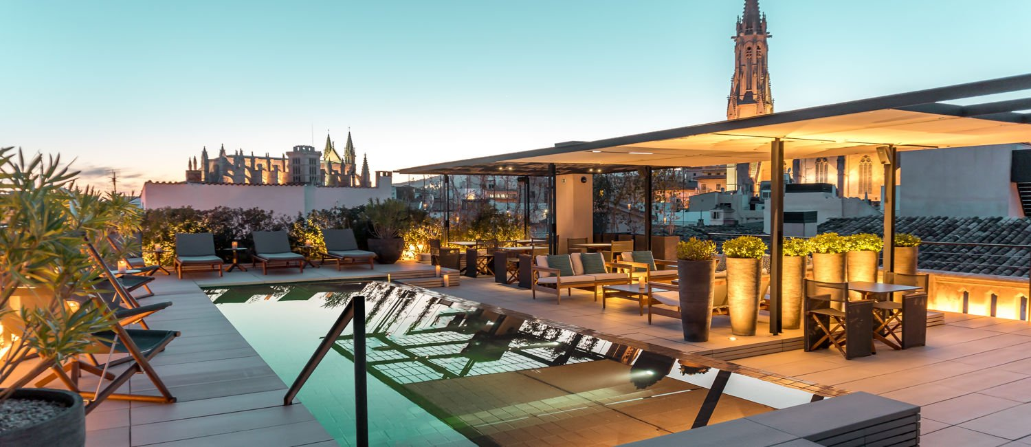 Roof terrace with pool and lounge chairs in the early evening of Sant Francesc boutique hotel in Palma
